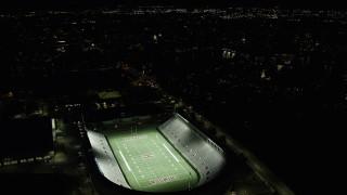 AX141_111 - 6K stock footage aerial video flying by Harvard Stadium and bridges, Harvard University, Massachusetts, night
