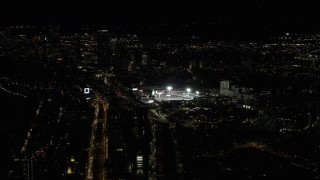 AX141_128 - 6K stock footage aerial video of a baseball game in progress, Fenway Park, Downtown Boston, Massachusetts, night