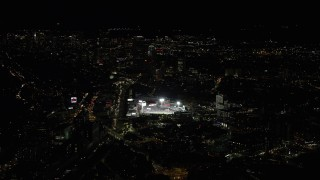AX141_129 - 6K stock footage aerial video flying by skyscrapers, baseball game, Fenway Park, Downtown Boston, Massachusetts, night