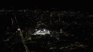 AX141_130 - 6K stock footage aerial video flying by baseball game, skyscrapers, Fenway Park, Downtown Boston, Massachusetts, night