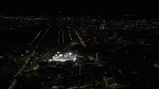 AX141_131 - 6K stock footage aerial video of a baseball game in progress at Fenway Park, Downtown Boston, Massachusetts, night