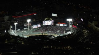 AX141_132 - 6K stock footage aerial video flying closely by baseball game at Fenway Park, Boston, Massachusetts, night