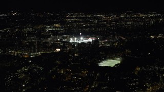 AX141_133 - 6K stock footage aerial video flying away from a baseball game, Fenway Park, Boston, Massachusetts, night