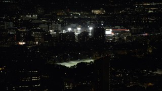 AX141_134 - 6K stock footage aerial video flying by buildings, skyscrapers, baseball game at Fenway Park, Boston, Massachusetts, night