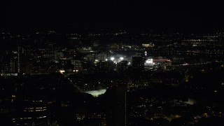 AX141_135 - 6K stock footage aerial video flying by downtown buildings, Fenway Park, Boston, Massachusetts, night