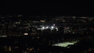 AX141_136 - 6K stock footage aerial video flying by bright lights of baseball game, Fenway Park, Boston, Massachusetts, night