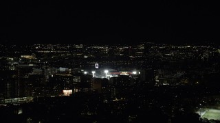 AX141_137 - 6K stock footage aerial video flying by buildings, bright lights of Fenway Park, Boston, Massachusetts, night