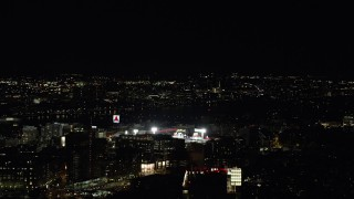 AX141_138 - 6K stock footage aerial video flying by buildings, skyscrapers, Fenway Park, Boston, Massachusetts, night