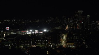 AX141_140 - 6K stock footage aerial video flying by baseball game at Fenway Park, skyline, Downtown Boston, Massachusetts, night