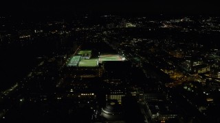AX141_169 - 6K stock footage aerial video approaching sports fields and Massachusetts Institute of Technology, Cambridge, Massachusetts, night