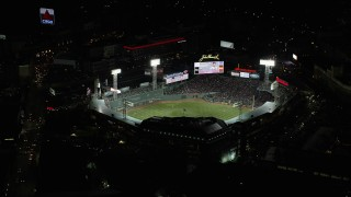 AX141_180 - 6K stock footage aerial video flying away from baseball game, Fenway Park, Boston, Massachusetts, night