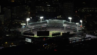 AX141_186 - 6K stock footage aerial video orbiting a crowded baseball game, Fenway Park, Boston, Massachusetts, night