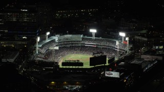 AX141_187 - 6K stock footage aerial video orbiting baseball game and busy city streets, Fenway Park, Boston, Massachusetts, night