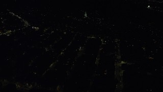 AX141_221 - 6K stock footage aerial video flying by Dorchester Heights Monument, city lights, South Boston, Massachusetts, night