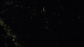 AX141_222 - 6K stock footage aerial video flying by city lights, Dorchester Heights Monument, South Boston, Massachusetts, night