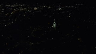 AX141_223 - 6K stock footage aerial video orbiting Dorchester Heights Monument, reveal skyline, South Boston, Downtown Boston, Massachusetts, night