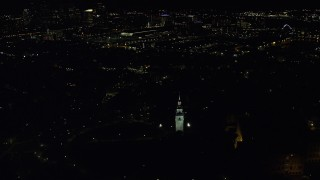 AX141_224 - 6K stock footage aerial video orbiting Dorchester Heights Monument, skyline, South Boston, Downtown Boston, Massachusetts, night