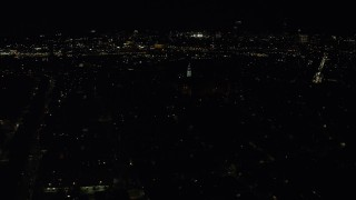 AX141_226 - 6K stock footage aerial video flying by Dorchester Heights Monument, skyline, South Boston, Downtown Boston, Massachusetts, night