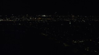 AX141_227 - 6K stock footage aerial video flying by Dorchester Heights Monument, skyline, South Boston, Downtown Boston, Massachusetts, night