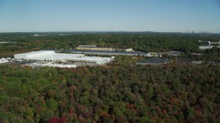 AX142_001 - 6K stock footage aerial video flying by warehouses surrounded by trees in autumn, Westwood, Massachusetts