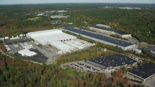 AX142_002 - 6K stock footage aerial video flying by warehouses surrounded by trees in autumn, Westwood, Massachusetts