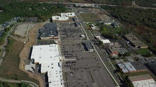 AX142_003 - 6K stock footage aerial video flying over a strip mall bordered by trees in autumn, Westwood, Massachusetts
