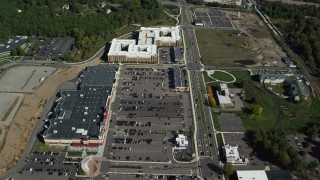 AX142_004 - 6K stock footage aerial video flying over strip mall and apartment building in autumn, Westwood, Massachusetts