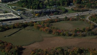 AX142_007 - 6K stock footage aerial video flying by Interstate 93, reveal buildings, trees, autumn, Westwood, Massachusetts