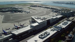 AX142_033 - 6K stock footage aerial video flying by parked planes, Logan International Airport, Boston, Massachusetts