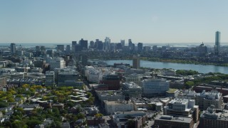 AX142_125 - 6K stock footage aerial video flying over MIT, by the skyline, Downtown Boston, Massachusetts
