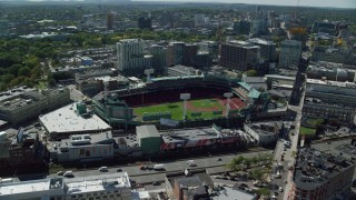 AX142_162 - 6K stock footage aerial video flying by Fenway Park on a sunny day, Boston, Massachusetts