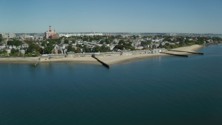 AX142_209 - 6K stock footage aerial video flying by coastal community, beach, breakwaters, South Boston, Massachusetts