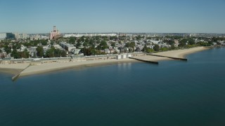 AX142_210 - 6K stock footage aerial video flying by coastal community, beach, breakwaters, South Boston, Massachusetts