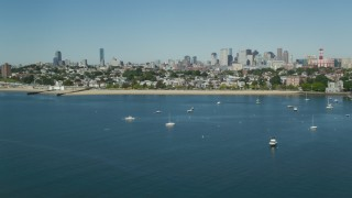AX142_215 - 6K stock footage aerial video flying by coastal community, anchored boats, skyline, South Boston, Massachusetts