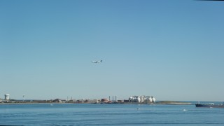 AX142_249 - 6K stock footage aerial video tracking a commercial plane flying over Boston Harbor, Massachusetts