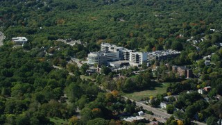 AX142_313 - 6K stock footage aerial video flying by Faulkner Hospital, colorful trees, autumn, Jamaica Plain, Massachusetts