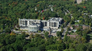 AX142_314 - 6K stock footage aerial video flying by Faulkner Hospital, colorful trees, autumn, Jamaica Plain, Massachusetts