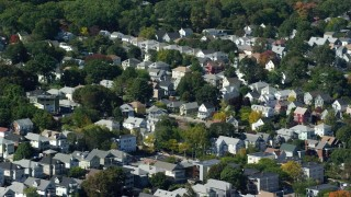 AX142_316 - 6K stock footage aerial video flying by a small residential town, green trees, Roslindale, Massachusetts