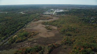 AX142_322 - 6K stock footage aerial video flying over forest, approach warehouse buildings, autumn, Dedham, Massachusetts
