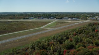 AX142_326 - 6K stock footage aerial video flying over trees in autumn, approaching Norwood Memorial Airport, Massachusetts