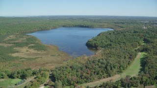 AX143_001 - 6K stock footage aerial video approaching and flying over Ponkapoag Pond, autumn, Canton, Massachusetts