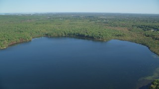 AX143_002 - 6K stock footage aerial video flying over Ponkapoag Pond, approaching forest, autumn, Canton, Massachusetts
