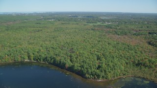 AX143_003 - 6K stock footage aerial video flying over Ponkapoag Pond, approach dense forest, autumn, Canton, Massachusetts