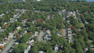 AX143_004 - 6K stock footage aerial video flying over small town neighborhoods, trees, autumn, Randolph, Massachusetts