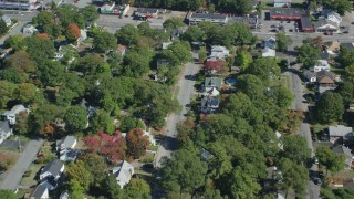 AX143_005 - 6K stock footage aerial video flying over small town neighborhood, trees, autumn, Randolph, Massachusetts