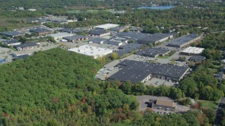 AX143_006 - 6K stock footage aerial video flying over forest, approach warehouse buildings, autumn, Braintree, Massachusetts
