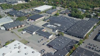 AX143_007 - 6K stock footage aerial video flying over warehouse buildings, parking lots, trees, Braintree, Massachusetts
