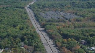 AX143_010 - 6K stock footage aerial video flying by Pilgrims Highway, condominium complex, autumn, Braintree, Massachusetts