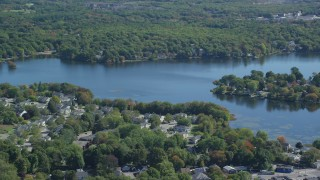 AX143_014 - 6K stock footage aerial video flying by small town, Whitmans Pond, autumn, Weymouth, Massachusetts