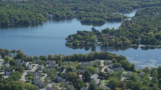 AX143_015 - 6K stock footage aerial video flying by small town, Whitmans Pond, autumn, Weymouth, Massachusetts